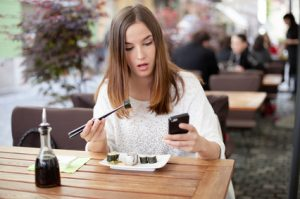 Young woman texting while eating sushi in a restaurant