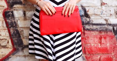Fashionable woman with red handbag in hands closeup