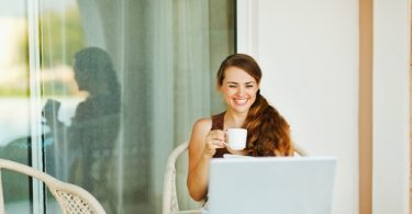 Laughing young woman enjoying cup of coffee and looking in laptop